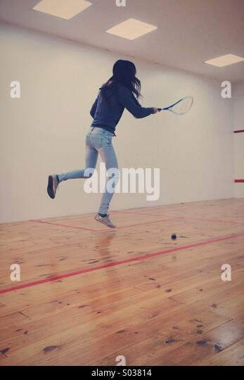 Graceful girl jumped when she has play squash in the sport room - Stock Image