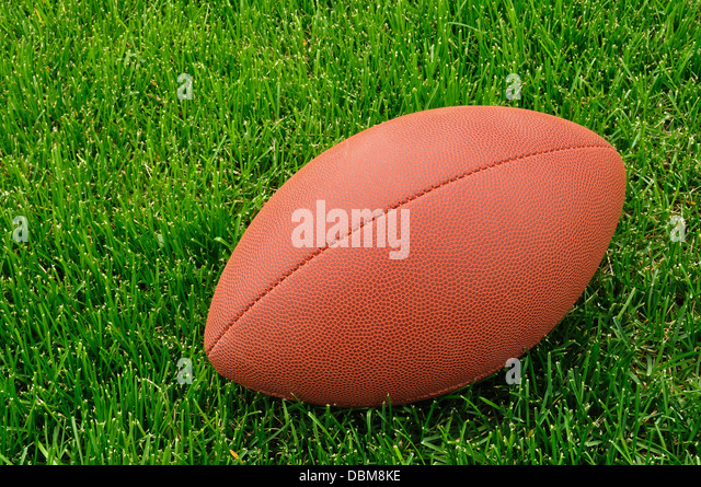 American football on a grass playing field - Stock Image