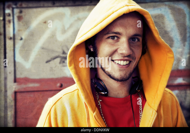 Teen / Young man portrait in hooded sweatshirt / jumper on grunge graffiti wall - Stock Image
