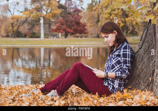 literature, young beautiful woman reading book in autumn park near the lake - Stock Image