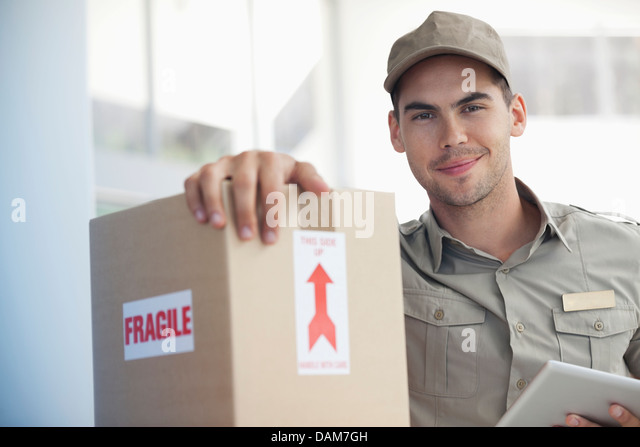 Delivery boy carrying 'fragile' package - Stock Image