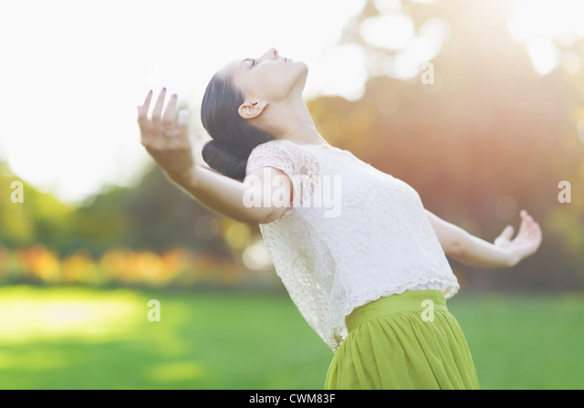 Young woman falling on meadow - Stock Image