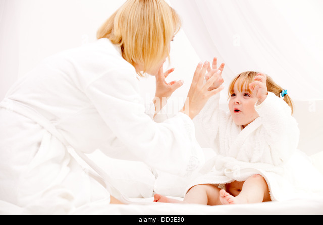 happy young mother playing with daughter on bed at home - Stock Image