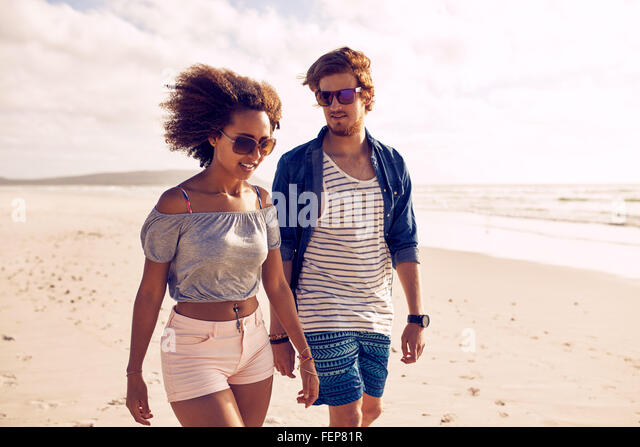 Portrait of young couple walking on the beach. Young man and woman strolling on the shoreline during the summertime. - Stock Image