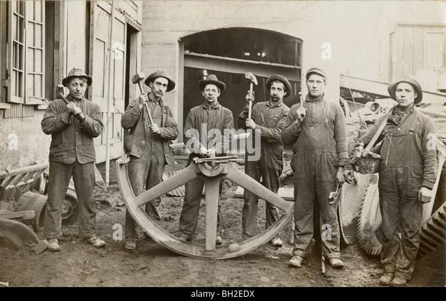 Six Laborers & Half of Giant Industrial Wheel - Stock Image