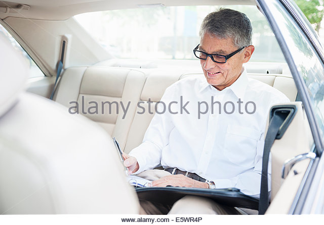 Senior adult businessman back seat of car, making notes - Stock-Bilder