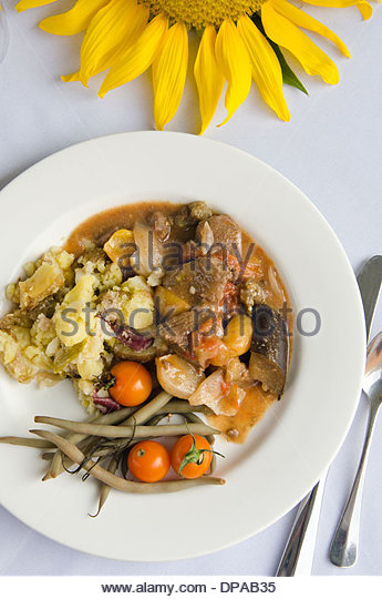 Late summer harvest stew with potatoes, beans and tomatoes on white plate with white tablecloth and sunflower. - Stock Image