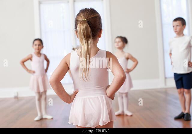 Four children practicing ballet with hands on hips in ballet school - Stock Image