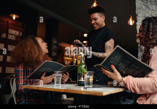 Cheerful two young women sitting at cafe holding menu card giving order to waiter. Young woman placing order to - Stock Image