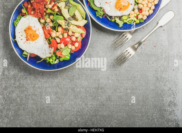 Healthy breakfast with fried egg, chickpea sprouts, seeds, vegetables and greens in blue ceramic bowls over grey - Stock Image