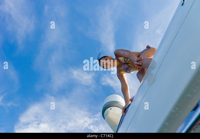 Girl on top of yacht, smiling, portrait - Stock Image