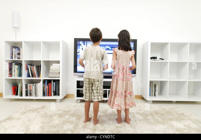 Boy and girl play video games on large 55 inch flat-screen television in white room - Stock Image