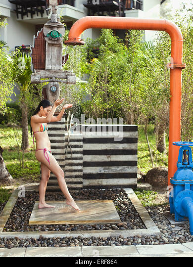 A woman showers under the pipe shower near the main pool at Indigo Pearl resort, Phuket, Thailand. - Stock-Bilder
