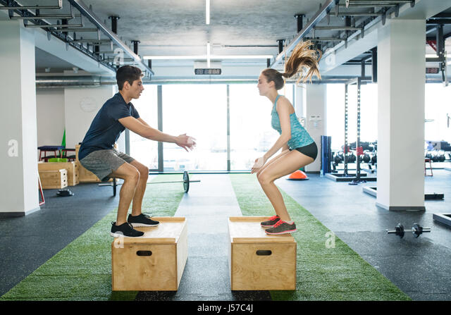 Young fit couple exercising in gym, doing box jumps. - Stock Image