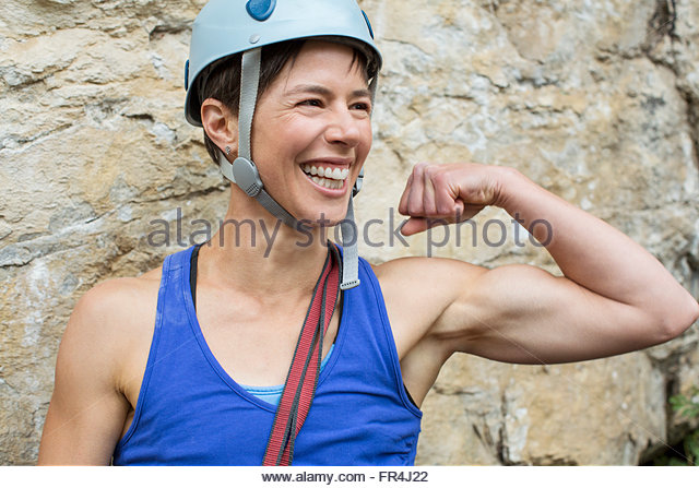 female rock climber showing off muscles - Stock Image