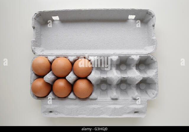 Eggs in packaging, missing eggs, half empty half full - Stock Image