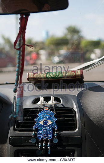 The all seeing eye and a Koran inside a taxi in Cairo Egypt - Stock Image