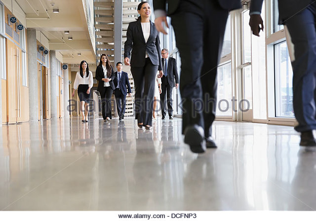 Group of business people walking in office building - Stock-Bilder