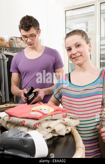 Young couple at cashpoint, smiling - Stock Image