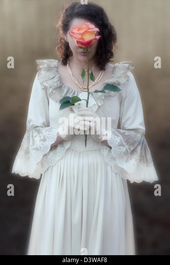 a lady in a victorian dress is holding a rose in front of her face - Stock Image