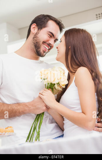Young man giving girlfriend white roses - Stock Image