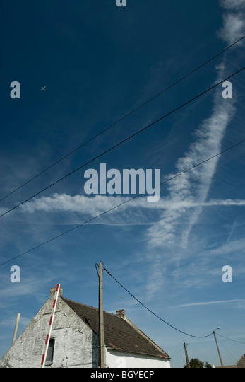 Vapor trails and airplane in blue sky above rustic house - Stock Image