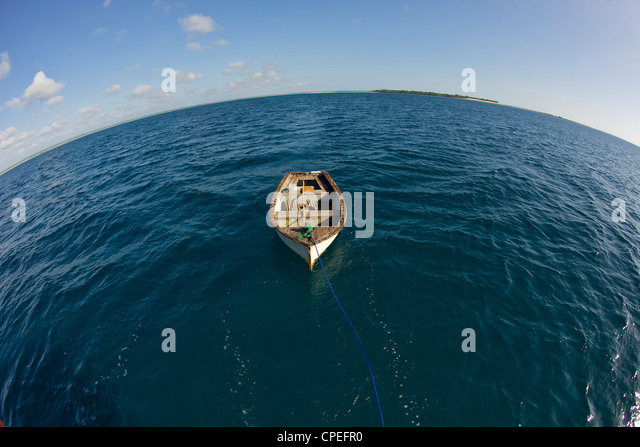 Row boat and Mogundula island in the Quirimbas archipelago in northern Mozambique. - Stock Image