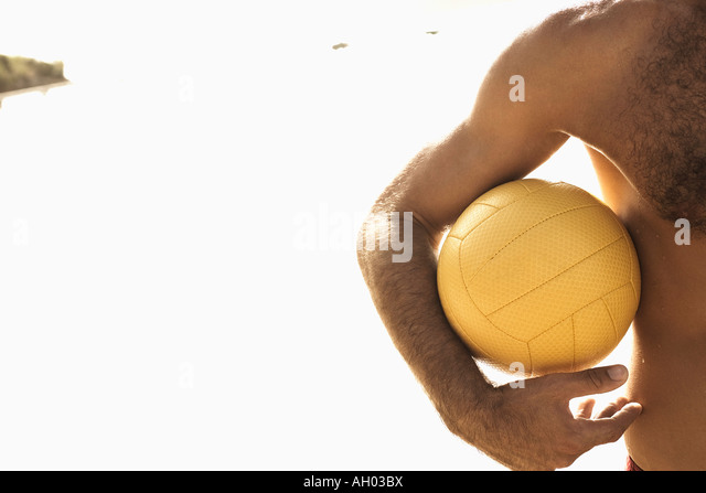 Mid section view of a man holding a beach volleyball on the beach - Stock Image