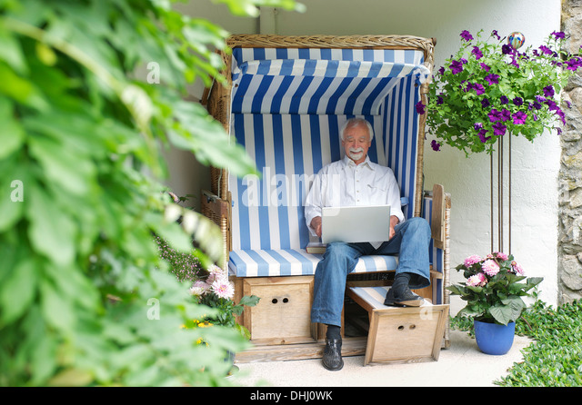 Senior man using laptop on garden seat - Stock-Bilder