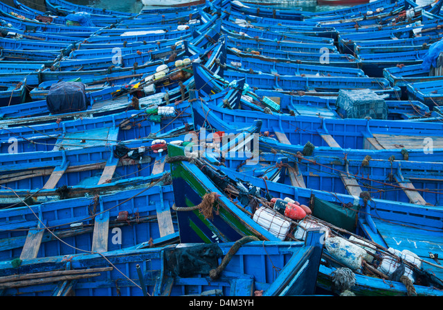Blue boats docked in harbor - Stock Image