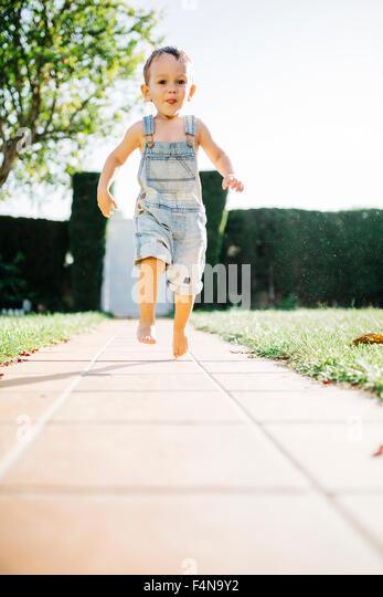 Little boy running barefoot on floor plates in the garden - Stock Image