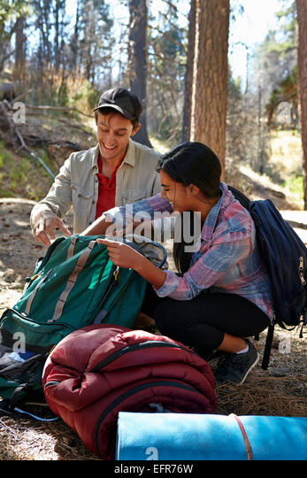 Young couple unpacking camping equipment in forest, Los Angeles, California, USA - Stock Image
