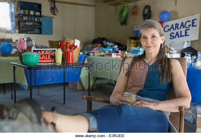 Woman with feet up at garage sale - Stock Image