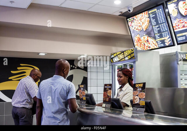 South Africa African Cape Town City Centre center Debonairs Pizza fast food inside counter Black woman employee - Stock Image