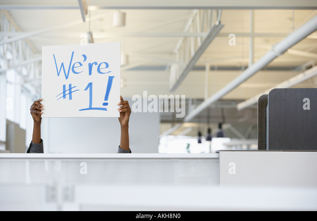 Office worker holding a sign - Stock-Bilder