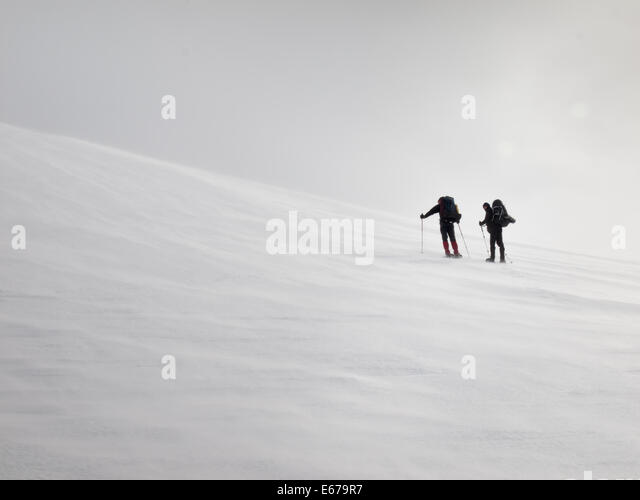 two men with heavy backpacks resting on a snow covered mountain slope in  winter. Huldraheimen, Gausdal Westfjel, - Stock Image