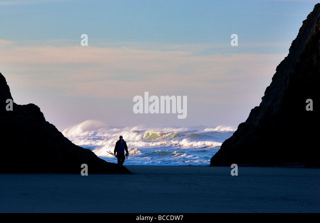 Waves and rock with photographer at Bandon Beach Oregon - Stock Image