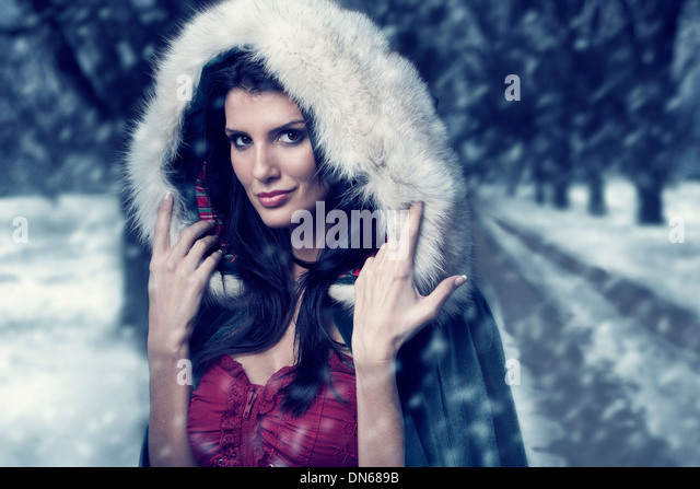 Woman in cape with hood standing on wooded path in the snow - Stock-Bilder