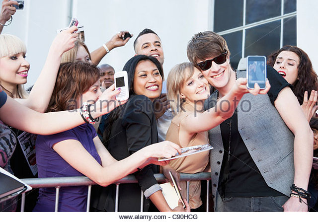 Celebrity taking pictures with fans - Stock Image