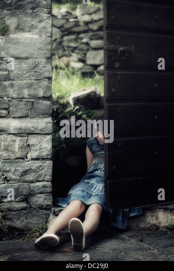 a sad, young girl is sitting in an old door - Stock Image