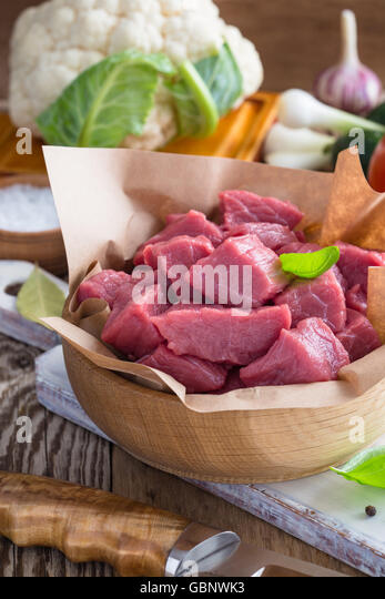Raw veal cut into pieces with vegetables and other ingredients ready to cook on wooden rustic table, organic cooking - Stock Image