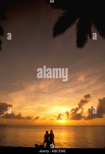Tropics tropical beach couple on deserted beach at sunrise sunset - Stock Image