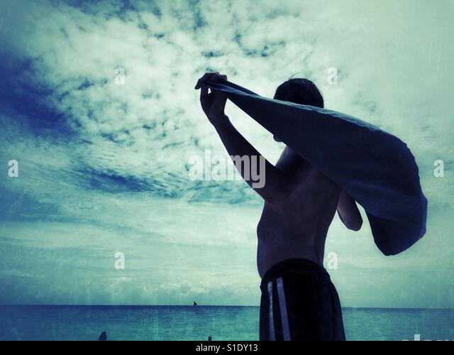 Man holding a towel around his shoulders after swimming off Puka Beach, Boracay Island, Philippines - Stock-Bilder