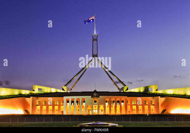 Building of Parliament on Capitol hill in Canberra - facade, entrance and columns illuminated with tall mast and - Stock Image