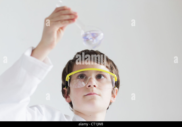 Student examining beaker of liquid - Stock Image