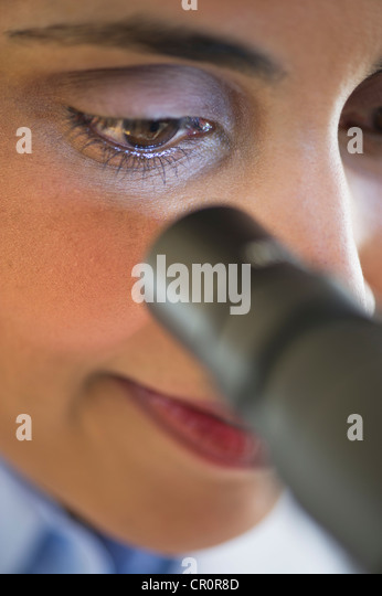USA, New Jersey, Jersey City, Scientist looking through microscope - Stock Image