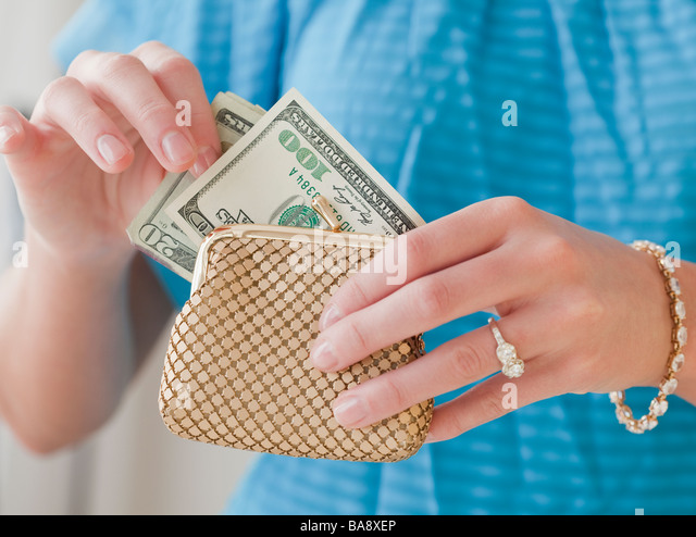 Woman pulling money from change purse - Stock Image