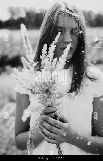Russia, Teenage girl (14-15) with bouquet of grass - Stock Image
