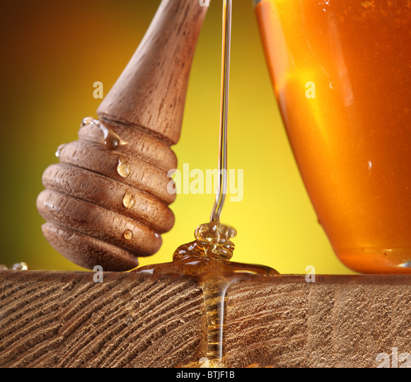 Wooden stick with honey drops on it is near the pot of honey; honey stream flowing on a wooden table. - Stock Image
