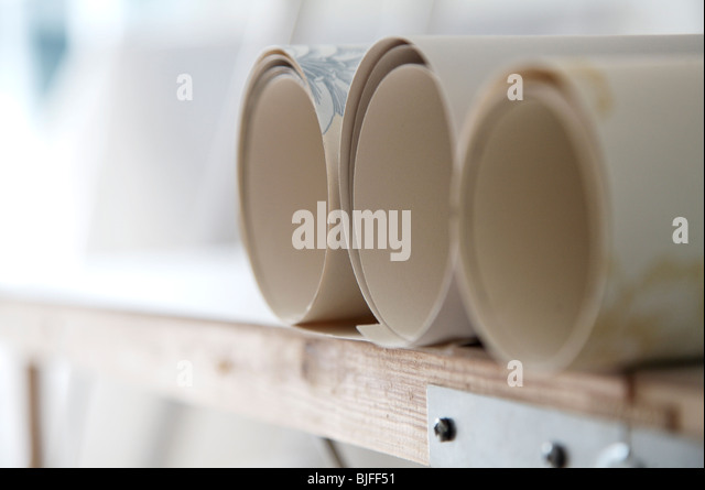 Three rolls of wallpaper on pasting table - Stock Image